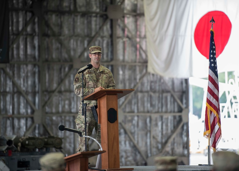 A U.S. service member stands behind a podium on a stage.