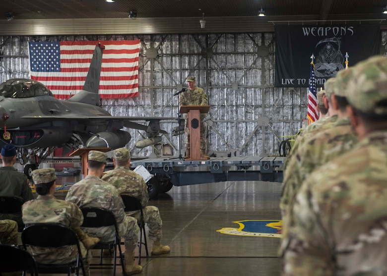 A service member stands behind a podium on a stage in hangar with an airplane and U.S. flag behind him on the left. Other service members are listening to him speak.
