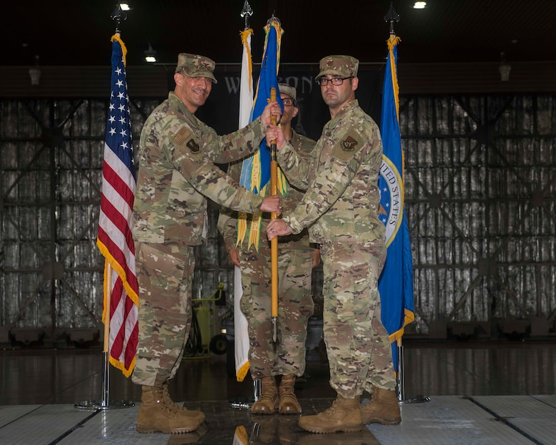 A male service member takes a guidon from another male service member.