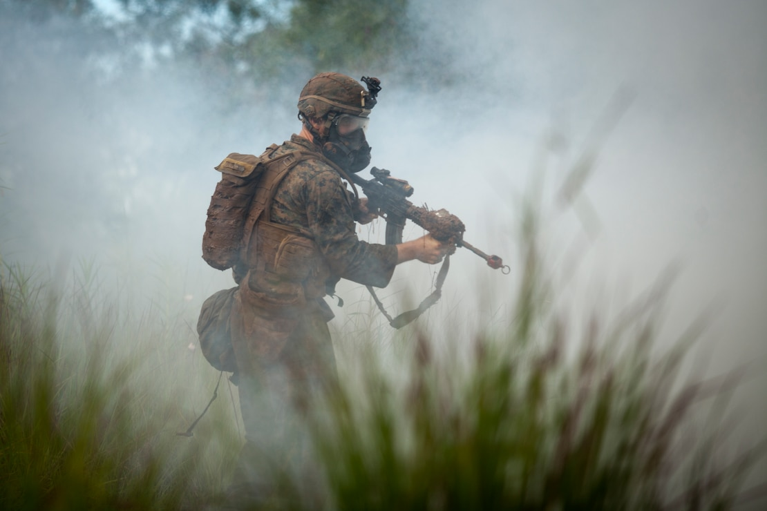 U.S. Marine Cpl. James K. Gordan II, a rifleman with 1st Battalion, 7th Marine Regiment, reacts to a surprise gas attack during the Advanced Infantry Course aboard Kahuku Training Area, Hawaii, July 20, 2016. AIC is intermediate training designed to enhance and test the Marine's skills and leadership abilities as squad leaders in a rifle platoon.