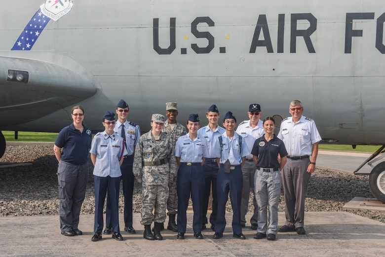 People pose for a group picture in front of an aircraft display