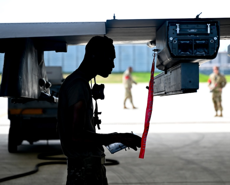 A silhouetted Airman works on an airplane.