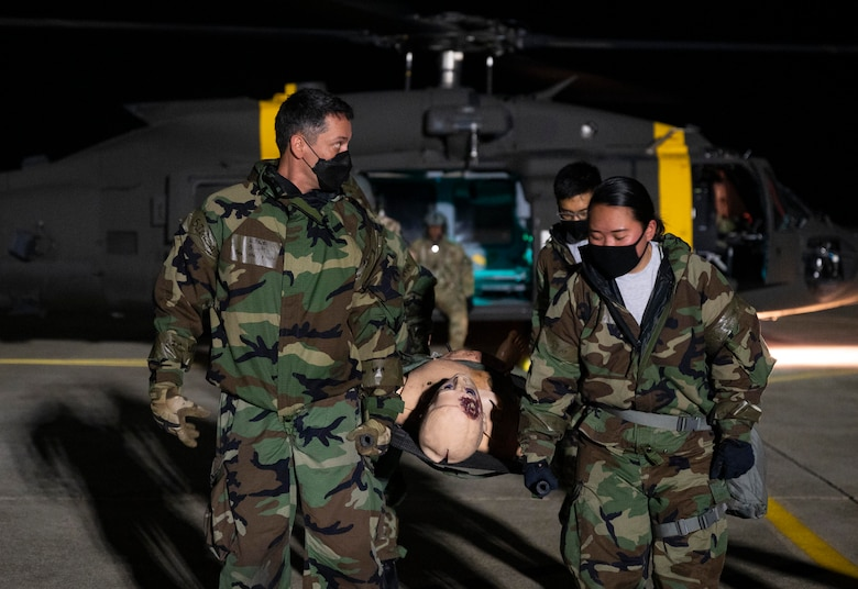 8th Medical Group Airmen transport simulated patient to HH-60M medevac helicopter.