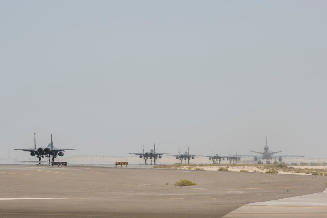 A KC-10 and 5 F-15s taxi down the runway