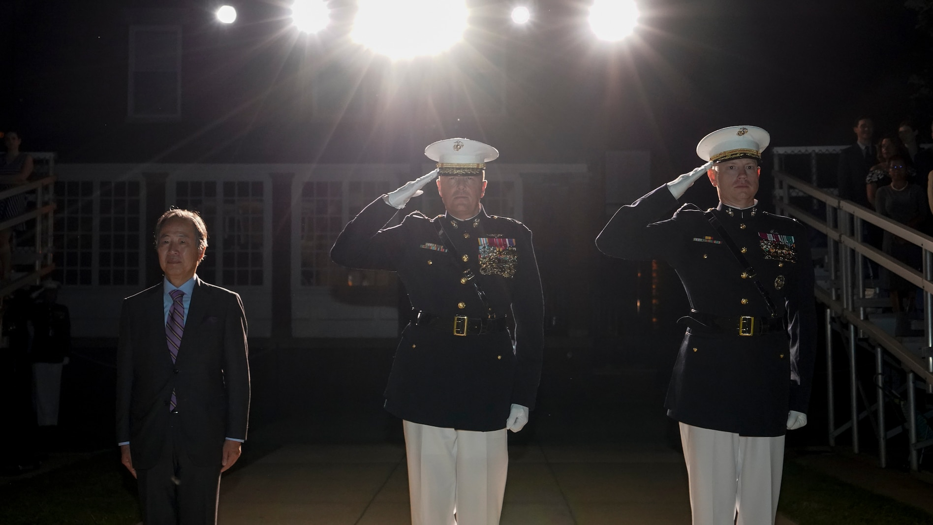 From left, Koji Tomita, Ambassador Extraordinary and Plenipotentiary of Japan to the United States, Lt. Gen. Mark R. Wise, Deputy Commander for Aviation, and Col. Teague A. Pastel, the commanding officer of Marine Barracks Washington, stand at the position of attention and render a salute during the Friday Evening Parade at MBW, July 23, 2021.