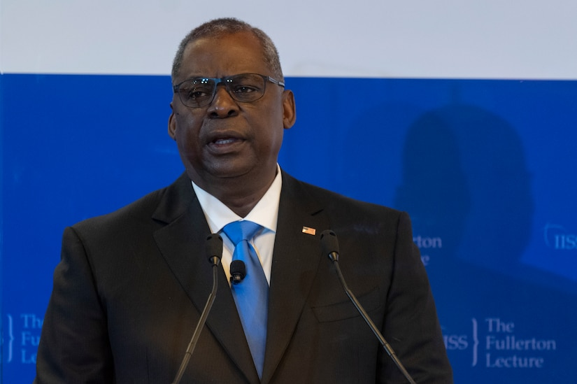 A man in a suit speaks at a podium.