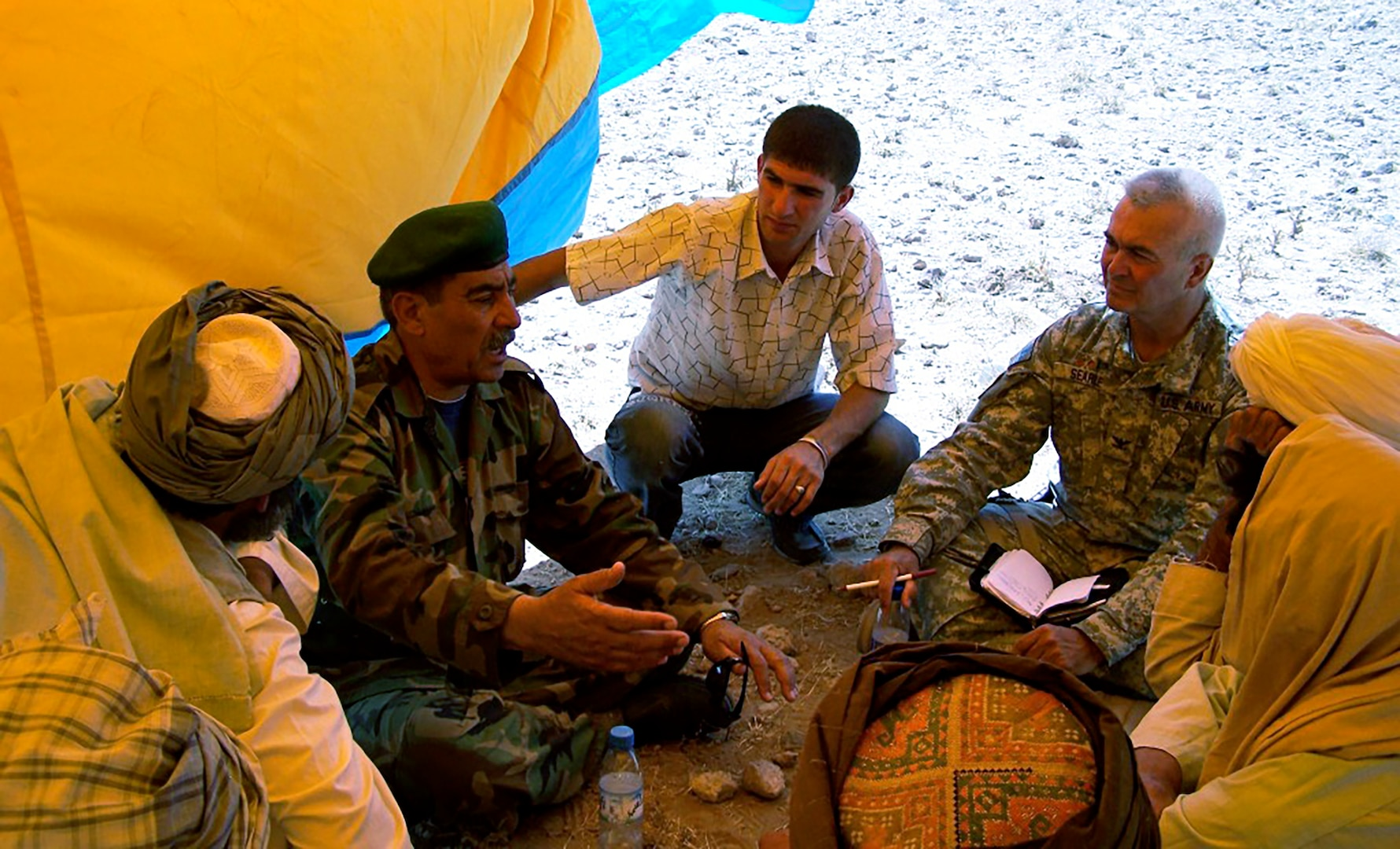 While serving as an interpreter for the U.S. military, Fahim Masoud (center), went on several missions with senior U.S. Army officers for meetings with local Afghanistan officials.