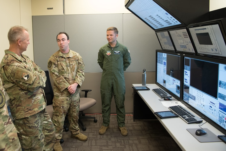 Three men standing in a room with computer screens behind them.
