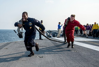Command Master Chief Keith Wilkerson, left, and Capt. Shane Marchesi, the executive officer of the aircraft carrier USS Harry S. Truman (CVN 75) compete in a fuel line hauling race during flight deck olympics.
