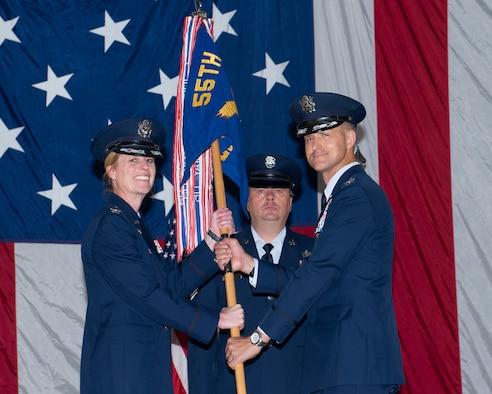 Uniformed female hands uniformed male the unit's guidon.