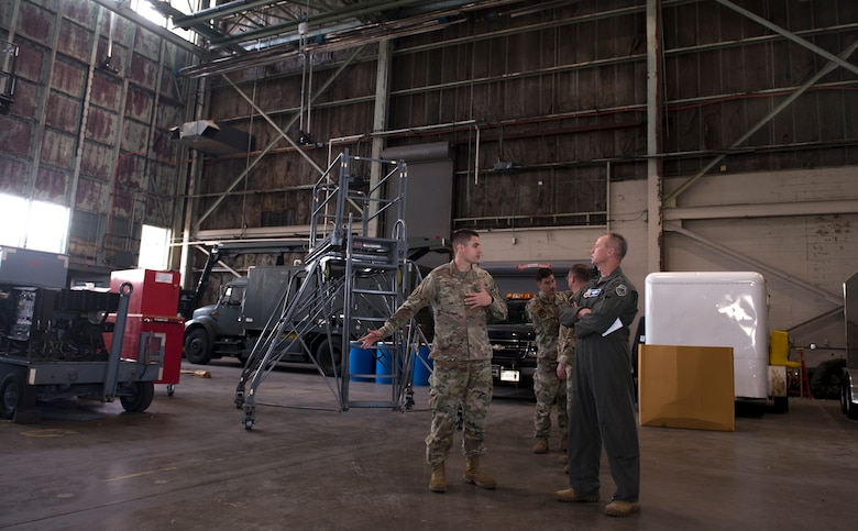 Two men in Air Force uniforms talk in an aircraft hangar.