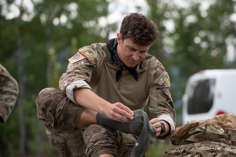U.S. Air Force Staff Sgt. Garrett Geske, tactical air control party (TACP) specialist, 3rd Air Support Operations Squadron, changes his socks after completing a land navigation event during the Chaos Challenge 2021 at Joint Base Elmendorf-Richardson, Alaska, July 14, 2021. The Chaos Challenge 2021 was a multi-day series of mental and physical contests sponsored by the 1st Air Support Operations Group with participants from the 3rd, 5th, 25th, and 604th Air Support Operations Squadrons and a guest team from the 673d Security Forces Squadron. The winner of the competition will go on to compete in Lightning Challenge 2021 to determine the best two-man TACP team in the Air Force.