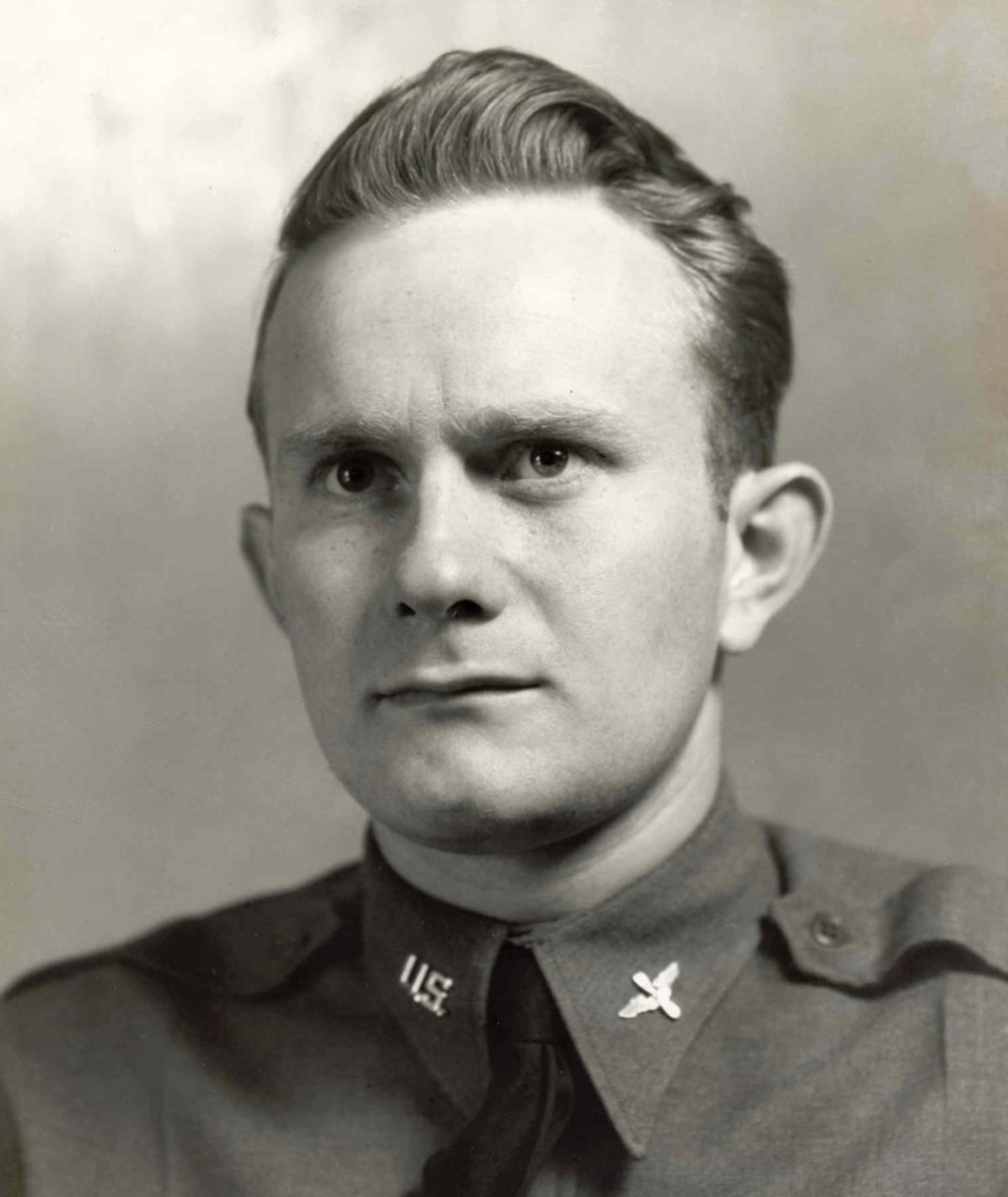 A man in a service jacket looks toward the camera.
