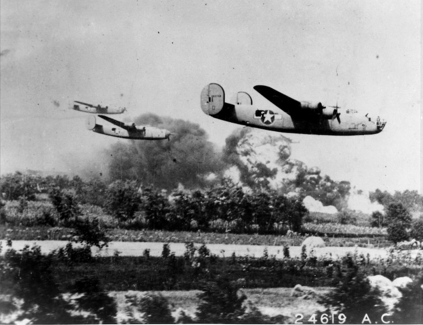Three bomber aircraft fly low over land. Large plumes of smoke and fire are visible in the background.