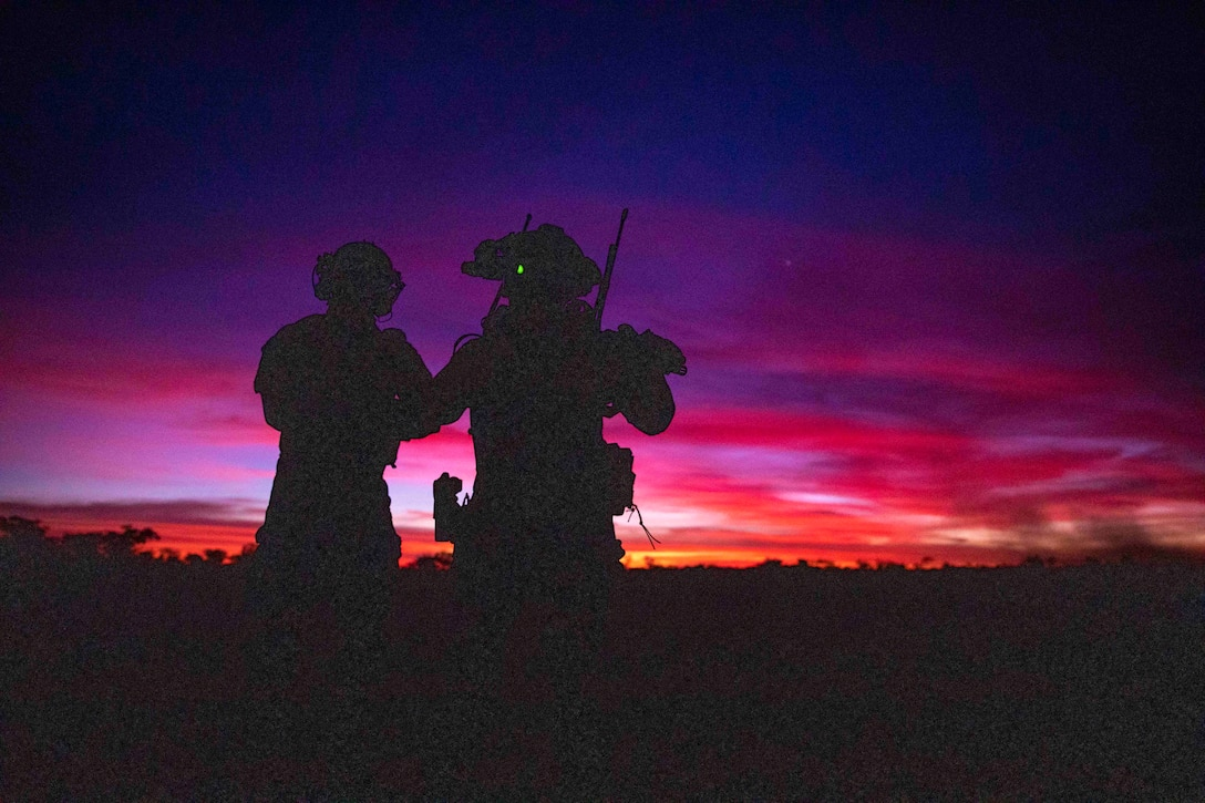 Two airmen shown in silhouette.