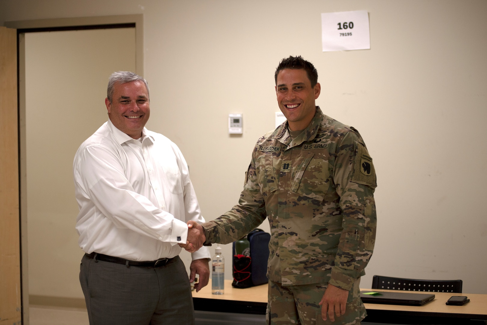 Capt. Danny Sluscharuk, Defense Cyber Operations Element chief with the Oklahoma National Guard defensive cyber operations team, shakes hands with Oklahoma State Bureau of Investigation Lt. Michael Dean, director of the OSBI Fusion Center, during Cyber Shield 2021 at the Norman Armed Forces Reserve Center, Norman, Oklahoma, July 21, 2021. Cyber Shield 21 focused on working in collaboration with state agencies to identify and defend against cyber threats that compromise local and national security. (Oklahoma National Guard photo by Sgt. 1st Class Mireilie Merilice-Roberts)