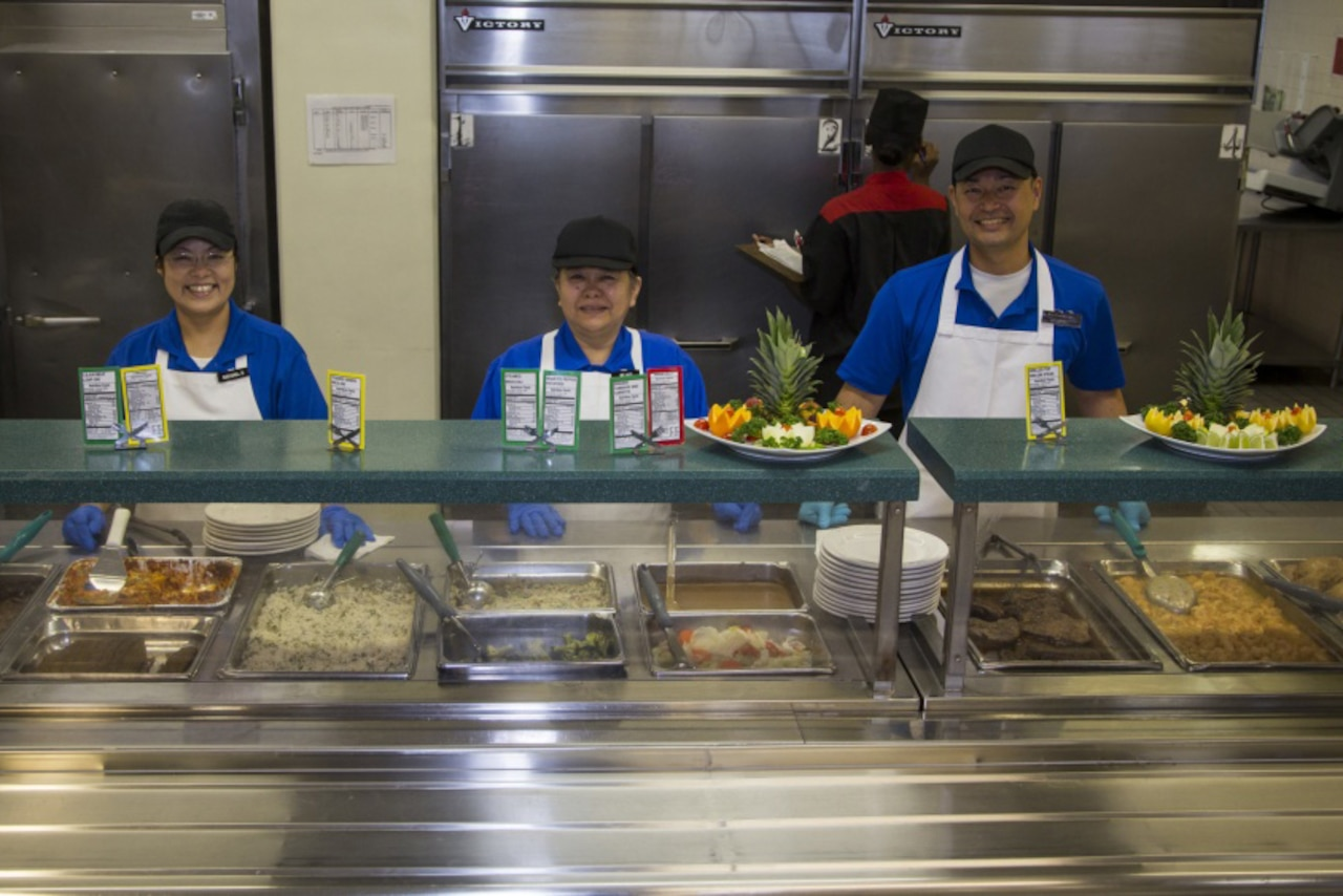Three people stand behind the serving line at a cafeteria.