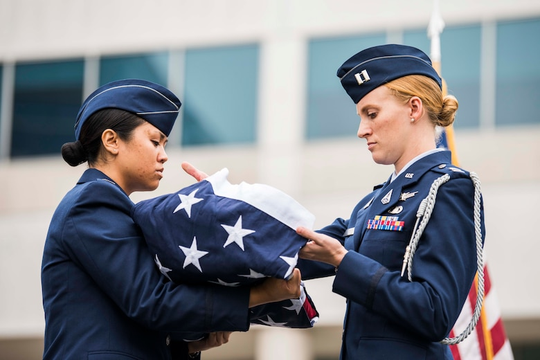 U.S. Space Force Captains Hannah Best and Kim Panagsagan, Space and Missile Systems Center officers, perform a ceremonial folding of the American flag during a retirement ceremony for U.S. Air Force Lt. Gen. John F. Thompson, SMC commander and Department of the Air Force Program Executive Officer for Space, at Los Angeles Air Force Base, California on July 27, 2021. Giving the flag a distinctive fold is a display of respect and gratitude to the individuals who fought, and continue to fight for freedom, at home and abroad. (U.S. Space Force photo by Staff Sgt. Luke Kitterman)