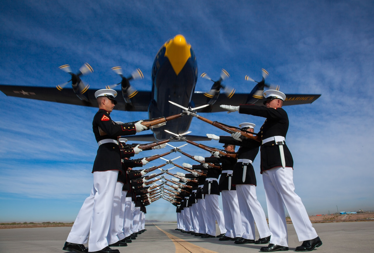 A group of Marine do rifle drills on a flightline as a blue aircraft flies low overhead.