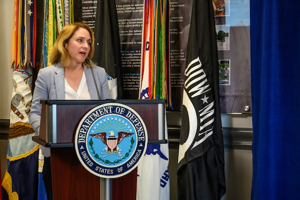 A woman stands behind a lectern.  Behind her is a flag with the POW/MIA logo.