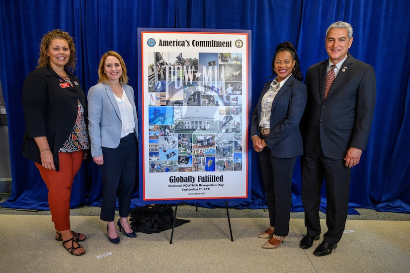 Deputy Defense Secretary Kathleen H. Hicks and other officials stand by a poster on display.