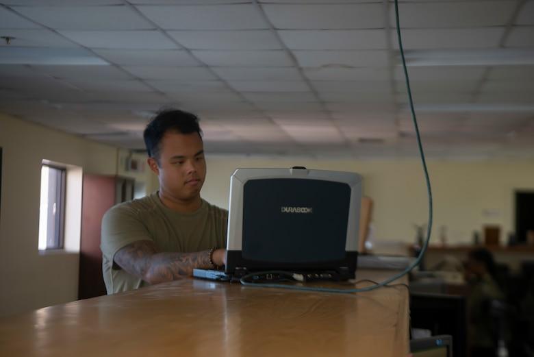 An Airman works on a computer to configure radar settings.