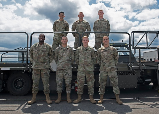 (From left, top to bottom) U.S. Air Force Tech. Sgt. Emmanuel Escobar, Senior Airman Connor Dickson, Senior Airman Hayden Floyd, Staff Sgt. Wesley Valentine, Tech. Sgt. Ronald West, Senior Airman Trenton Dancer and Airman 1st Class Clay Huddleston, all members of the 62nd Aerial Port Squadron, pose for a photo at Joint Base Lewis-McChord, Washington, July 21, 2021. They make up the team of aerial port Airmen that will travel to Joint Base Pearl Harbor-Hickam, Hawaii, in August to compete in the 2021 Pacific Air Forces (PACAF) Port Dawg Rodeo. (U.S. Air Force photo by Senior Airman Zoe Thacker)