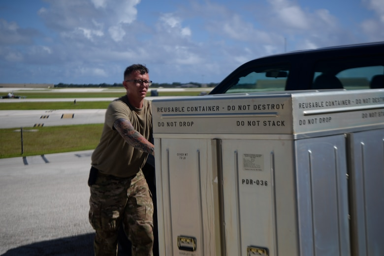 Airman pushes metal boxes full of equipment on a cart.