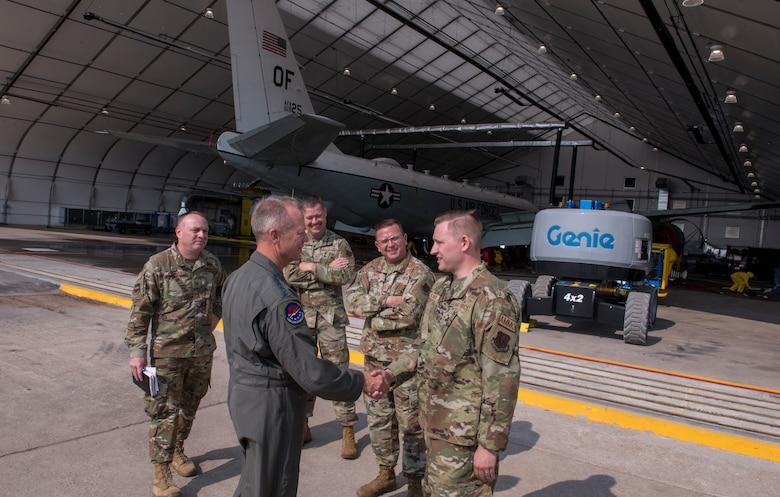 A group of uniformed Air Force Airmen talk and shake hands outside an aircraft hangar.