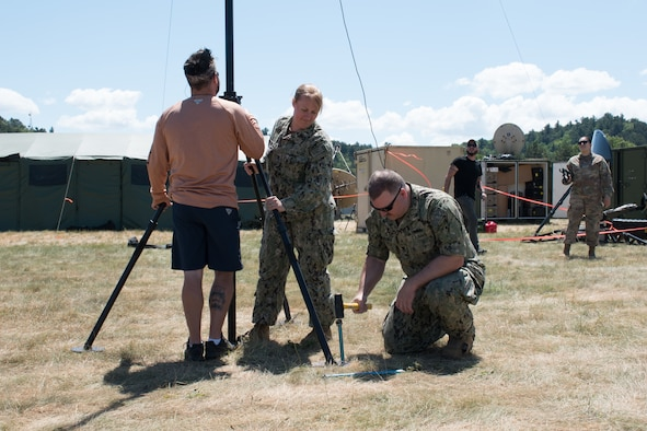 VOLK FIELD, Wis. (June 15, 2021) – Electronics Technician 1st Class Marshall Hundemer, Electronics Technician 2nd Class Amanda Yazzie, from Navy Central Command Mobile Ashore Support Team Dets A and B, and John Knorr, an infrastructure technician from Copper River Enterprise Services, install a HAM radio HF antenna on Volk Field, Wisconsin during exercise Patriot 21.  The HF antenna is being tested for interoperability from amateur HAM radio operators to military HAM radios during Patriot 21. Patriot 21 is a training exercise designed for civilian emergency management and responders to work with military entities in the same manner that they would during disaster. (U.S. Navy photo by Mass Communication Specialist 1st Class Sandi Grimnes Moreno)