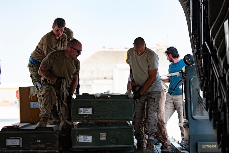 U.S. Airmen and members of the Kuwait Air Force load a case on a Kuwait Air Force C-17 Globemaster III at Ali Al Salem Air Base, Kuwait, July 26, 2021. One of the priorities of the 386th Air Expeditionary Wing is to foster enduring partnerships. These partnerships are built on mutual respect and critical to current and future missions. (U.S. Air Force Senior Airman Helena Owens)