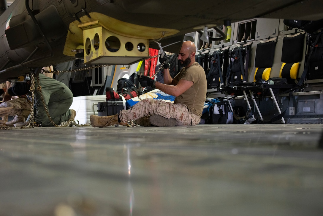 A Kuwait Air Force member secures an AH-64E APACHE inside of a Kuwait Air Force C-17 Globemaster III at Ali Al Salem Air Base, Kuwait, July 26, 2021. One of the priorities of the 386th Air Expeditionary Wing is to foster enduring partnerships. These partnerships are built on mutual respect and critical to current and future missions. (U.S. Air Force Senior Airman Helena Owens)