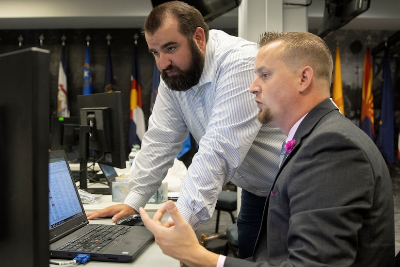Scott Ferge, U.S. Army Financial Management Command systems accountant, right, talks with Brian Hardesty, Defense Finance and Accounting Service general ledger branch division chief, during the Army's mock fiscal yearend closeout at the Maj. Gen. Emmett J. Bean Federal Center July 19. Mock yearend is an exercise designed to prepare the U.S. Army Financial Management Command and its partners, like DFAS, for the fiscal yearend closeout and financial statement preparation at the start of October. (U.S. Army photo by Mark R. W. Orders-Woempner)