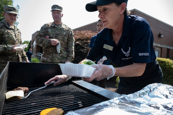 Vikki Richards, 911th Force Support Squadron cook, serves Airmen burgers during a burger burn at the Pittsburgh International Airport Air Reserve Station, Pennsylvania, July 27, 2021. The 911th FSS held the burger burn to thank Air Force Club members while trying to increase membership.