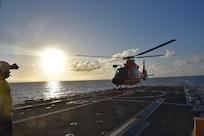 Crewmembers from the Coast Guard Cutter Harriet Lane conduct sunset flight operations with an MH-65 Dolphin aircrew from Coast Guard Air Station Miami in the Caribbean Sea.