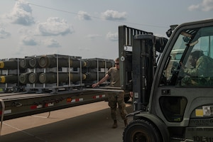 U.S. Air Force Airman Dylan Tyerman-Sterling, 509th Munitions Squadron munitions stockpile technician guides Airman 1st Class Isaiah Welch, 509th Munitions Squadron munitions stockpile technician, while unloading bomb bodies during exercise Quick Fuze at Whiteman Air Force Base, Missouri, July 20, 2021. Exercise Quick Fuze tests the munition squadron's ability to rapidly produce munitions to expeditiously arm every B-2 Spirit in the inventory.