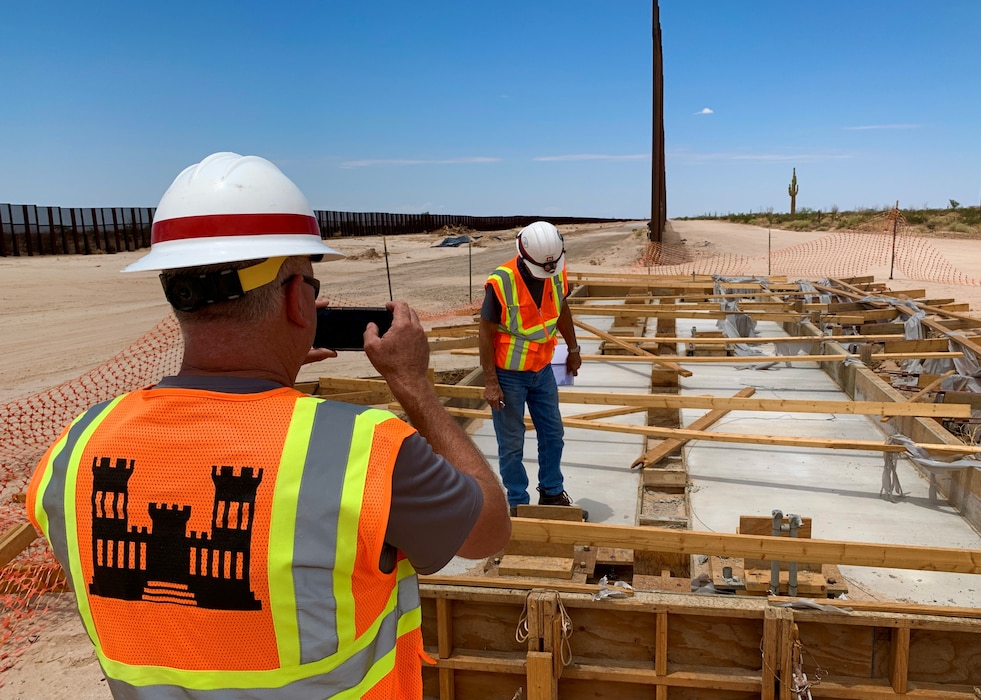 U.S. Army Corps of Engineers South Pacific Border District employees document an unfinished gate structure before work begins at the Yuma 10/27 former wall construction site near Yuma, Arizona, July 19. The District began safety work on July 15 at the Yuma 2 and Yuma 10/27 former wall construction sites in the U.S. Border Patrol's Yuma sector. This work will not involve expanding the border barrier and specific activities will include filling open trenches, cutting and capping conduit, making gate foundations safe, making maintenance roads safe, and grading around handholds and manholes.