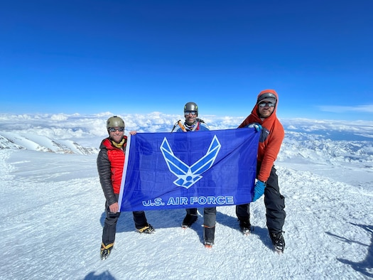 Left to right, Lt. Col. Rob Marshall, Lt. Col. Mark Uberuaga and Wes Morgan proudly display the Air Force flag on top of Denali, the highest mountain peak in North America. (Matt Wheat)