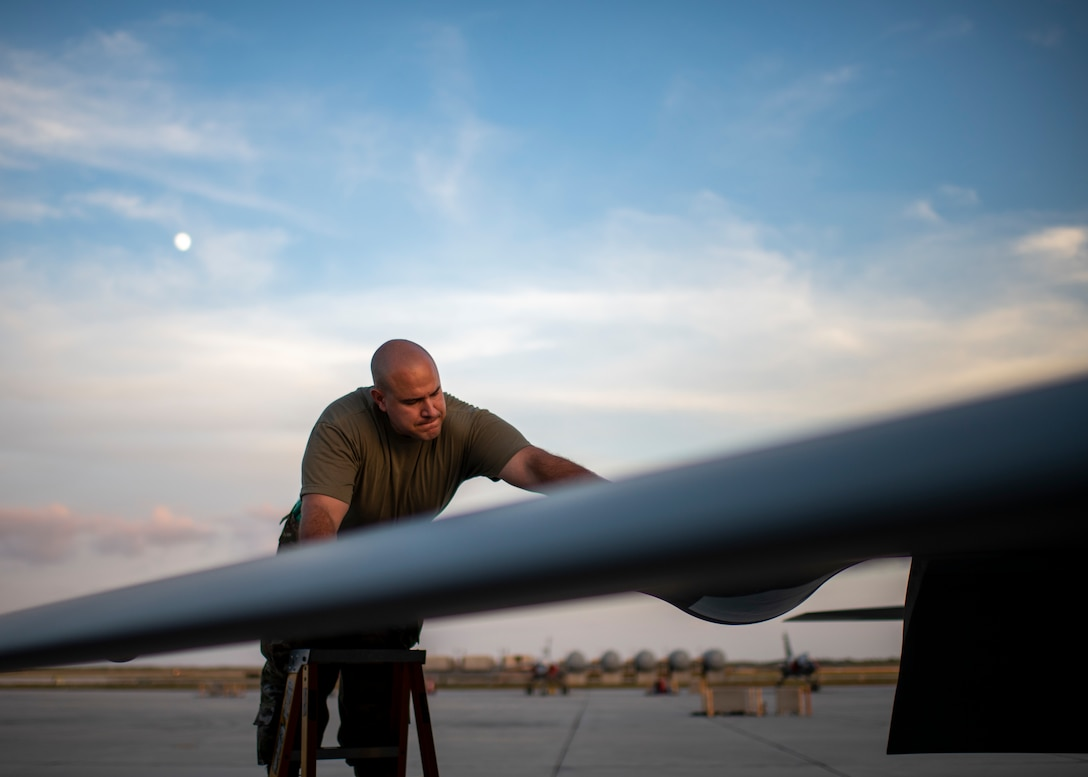 A man stands on a ladder near the wing of a plane
