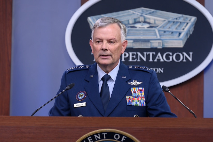 A  man wearing a military uniform stands at a lectern and appears to speak into two microphones.