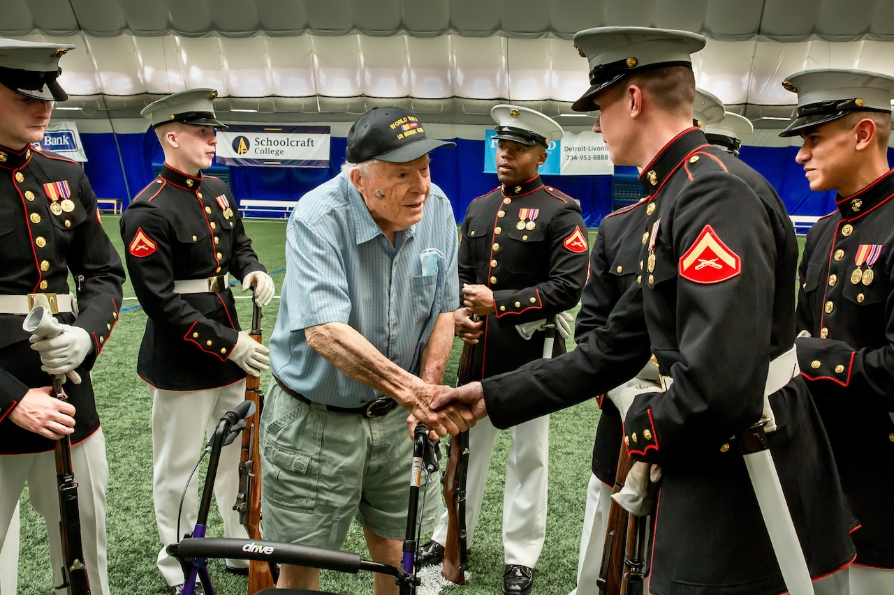 Members of a platoon meet with a veteran at a stadium.