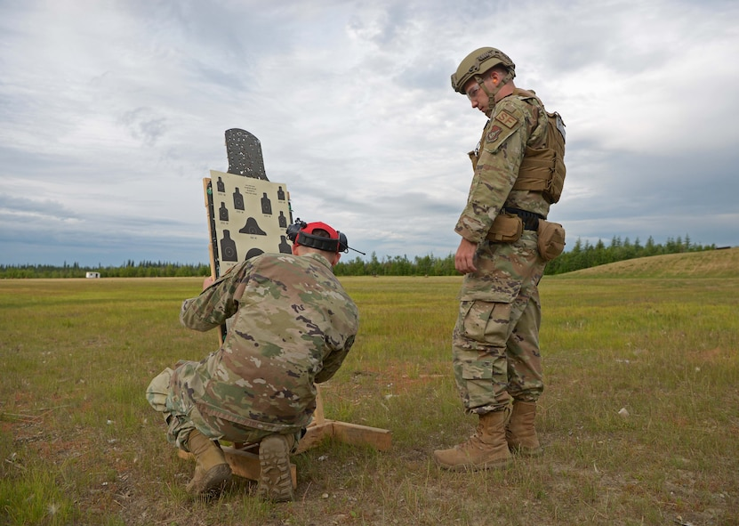 Airmen from the 354th Security Forces Squadron check a target during a new Security Forces Qualification Course on Eielson Air Force Base, Alaska, July 14, 2021. Throughout the course, Eielson Defenders and Combat Arms instructors will be giving feedback directly to the U.S. Air Force Security Forces Center at Lackland Air Force Base, Texas. (U.S. Air Force photo by Senior Airman Beaux Hebert)