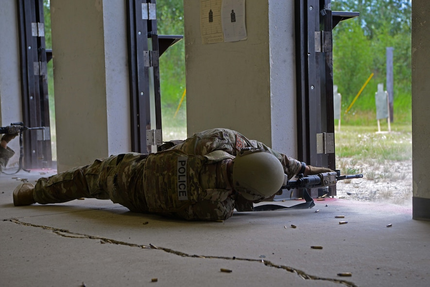 An Airman assigned to the 354th Security Forces Squadron fires an M4 carbine in a new firing position during a new Security Forces Qualification Course on Eielson Air Force Base, Alaska, July 14, 2021. In this proposed course, Defenders will fire from many different positions to simulate firing during an active shooter situation. (U.S. Air Force photo by Senior Airman Beaux Hebert)