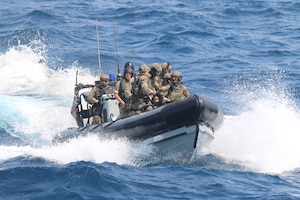 210721-N-N0146-1002 ARABIAN GULF (July 21, 2021) – Royal Navy Sailors and U.S. Navy Sailors operate a rigid hull inflatable boat during a multilateral air operations in support of maritime surface warfare (AOMSW) exercise in the Arabian Gulf, July 21. (U.S. Coast Guard photo by Petty Officer 2nd Class Joseph Perrone)