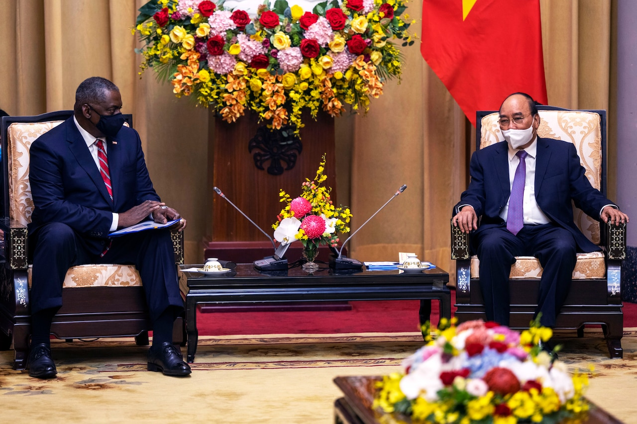 The U.S. Defense Secretary sits next to Vietnam's president during official discussions.