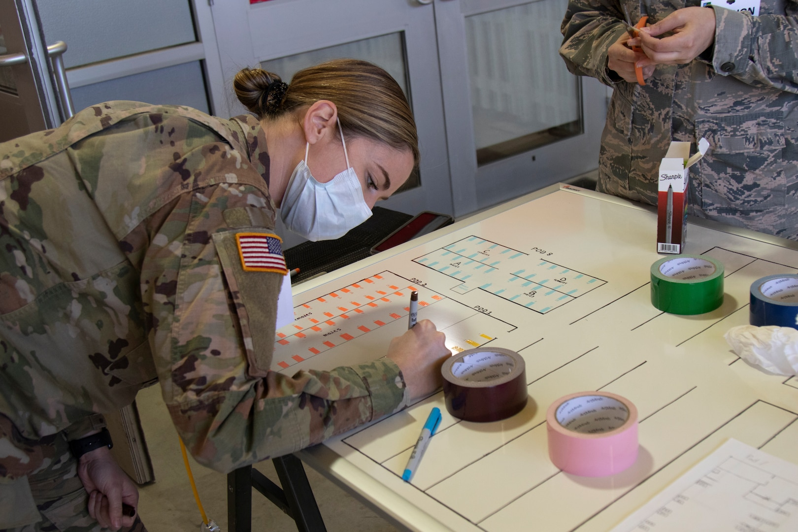 Army 1st Lt. Joan Emerson of Charlie Company, 186th Brigade Support Battalion, records the hospital beds that are part of each medical pod at the Alternate Healthcare Facility in Essex, Vermont, on April 7th, 2020. The Vermont National Guard is working with the state of Vermont and emergency partners in a whole-of-government effort to flatten the curve during the COVID-19 pandemic. (U.S. Army National Guard photo by Cpl. Gillian McCreedy)