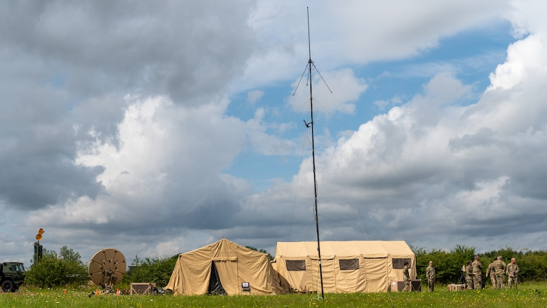 A distant view of Airmen standing next to tents and antenna.
