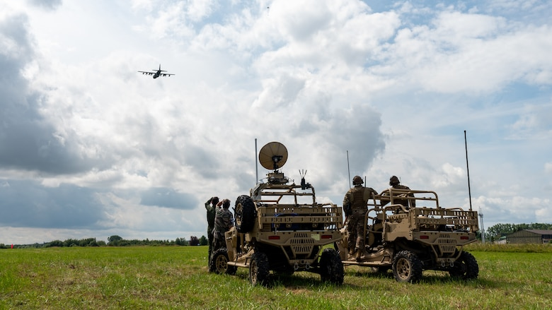 People standing next to vehicles in a field and looking at an aircraft flying in the distance.
