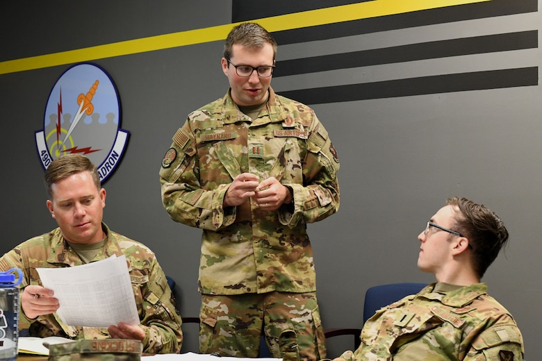 Capt. Alexander Maynard, center, 12th Missile Squadron intercontinental ballistic missile combat crew commander, briefs 12th MS ICBM combat crew members 2nd Lt. Jacob Wallace, left, and 1st Lt. Braxton Stocking, right, on their upcoming missile field deployment July 21, 2021, at Malmstrom Air Force Base, Mont.