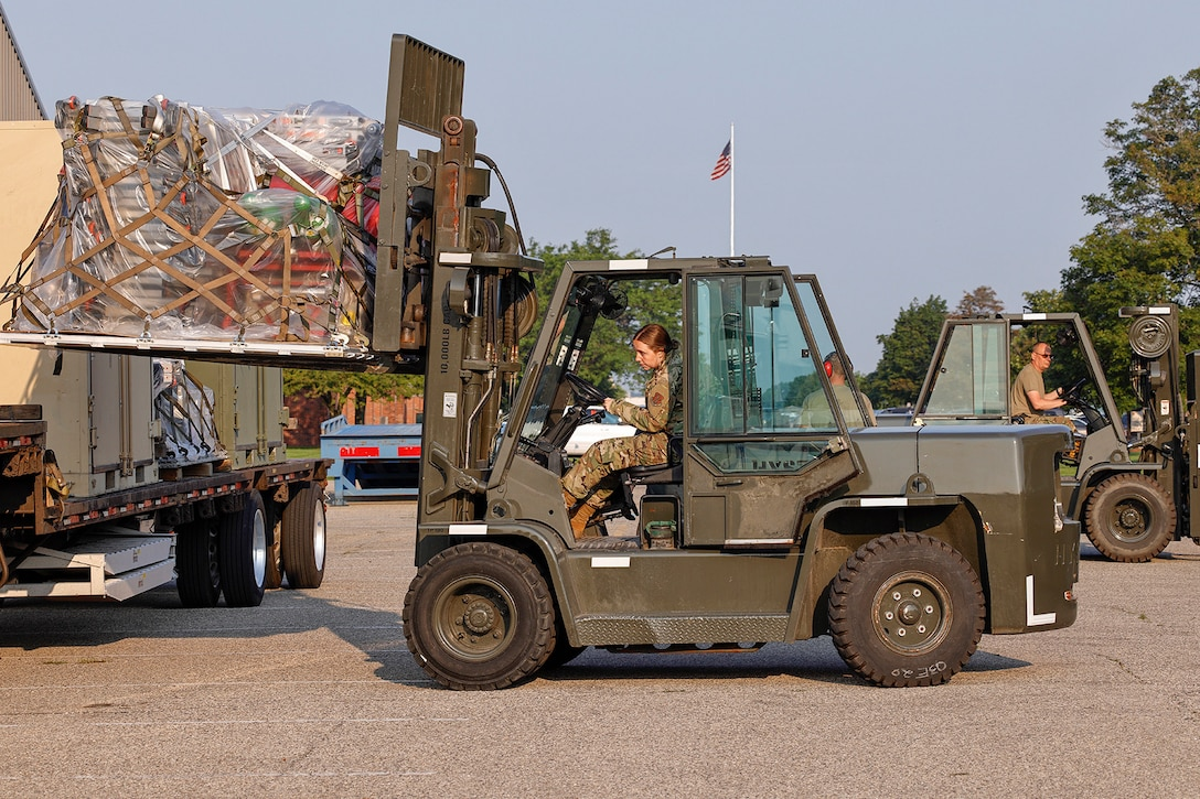 Airmen use forklifts to load equipment on a truck.